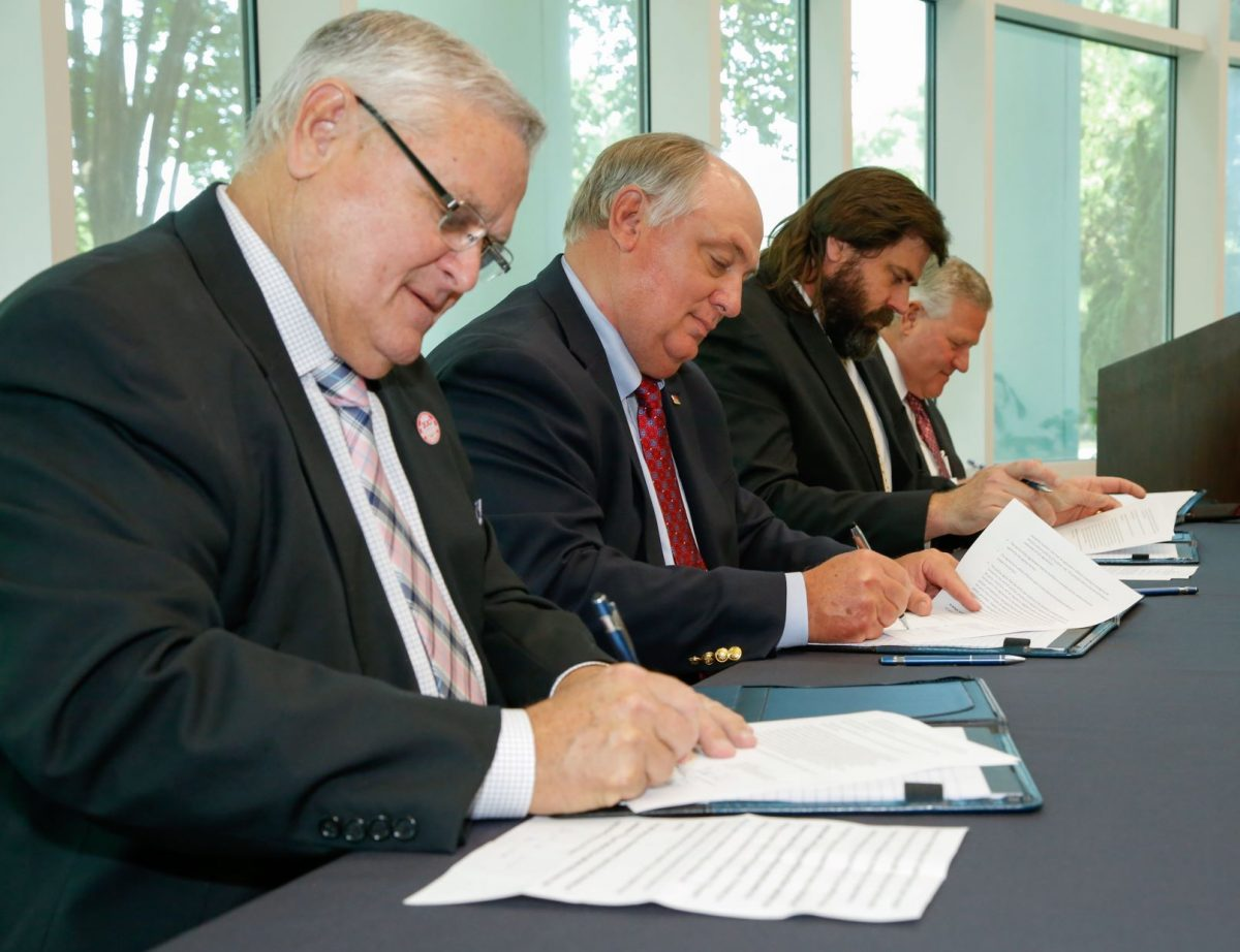 l-r Commissioner Rick Pate, Federation President Jimmy Parnell, NALC Director Harrison Pittman and Faulkner President Mike Williams sign a memorandum of understanding to establish a three-year Alabama Ag Law Pathway.