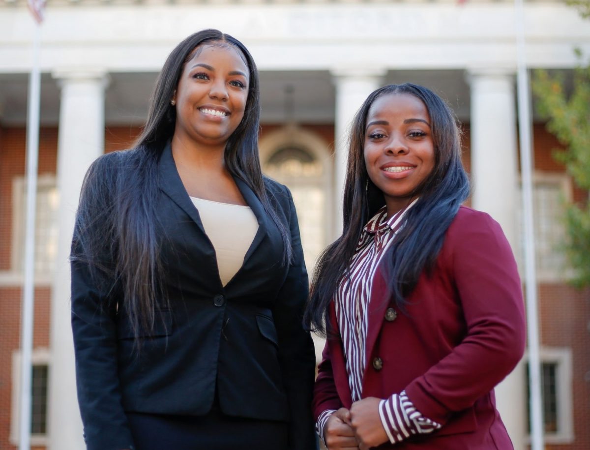 Faulkner Law graduate Aigner Kolom, left poses with Faulkner Law student Iesha Brooks in front of Montgomery City Hall.